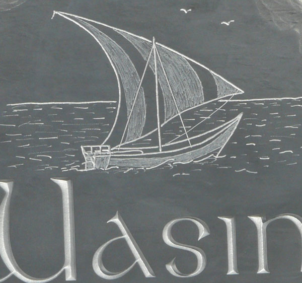 Close up of sand blasted lettering and hand drawn and engraved and textured artwork. All painted silver.